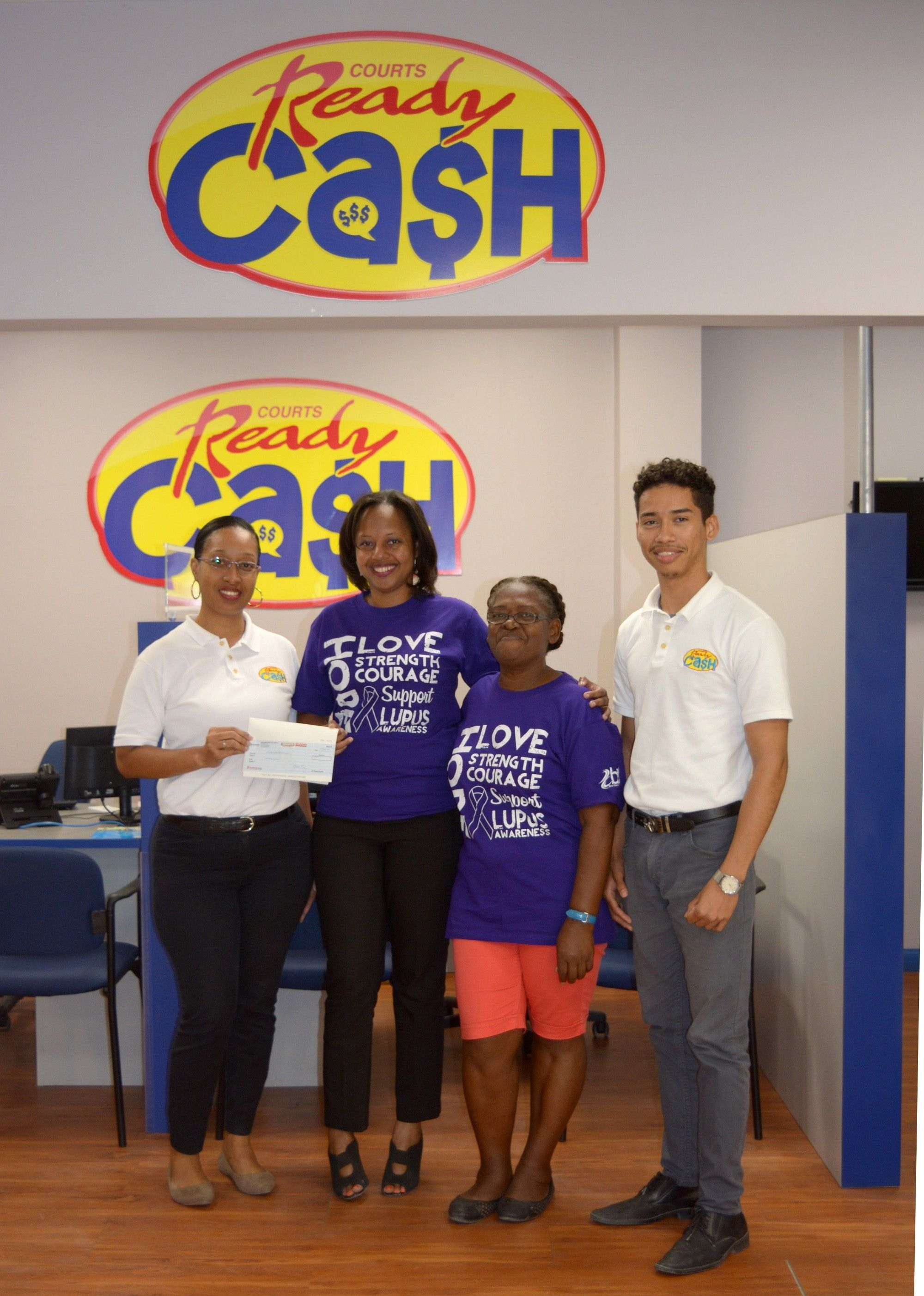Courts Ready Cash presents a cheque of $1,000 to the Lupus and RA Association of Belize.